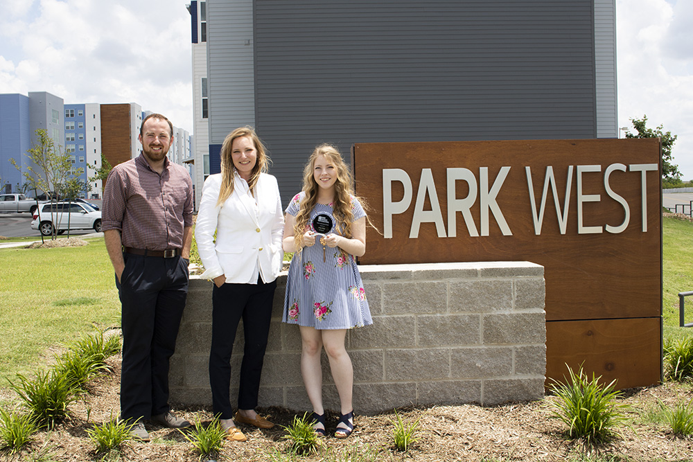 Park West employees show off the Keep Brazos Beautiful Green Business Award in front of the Park West sign
